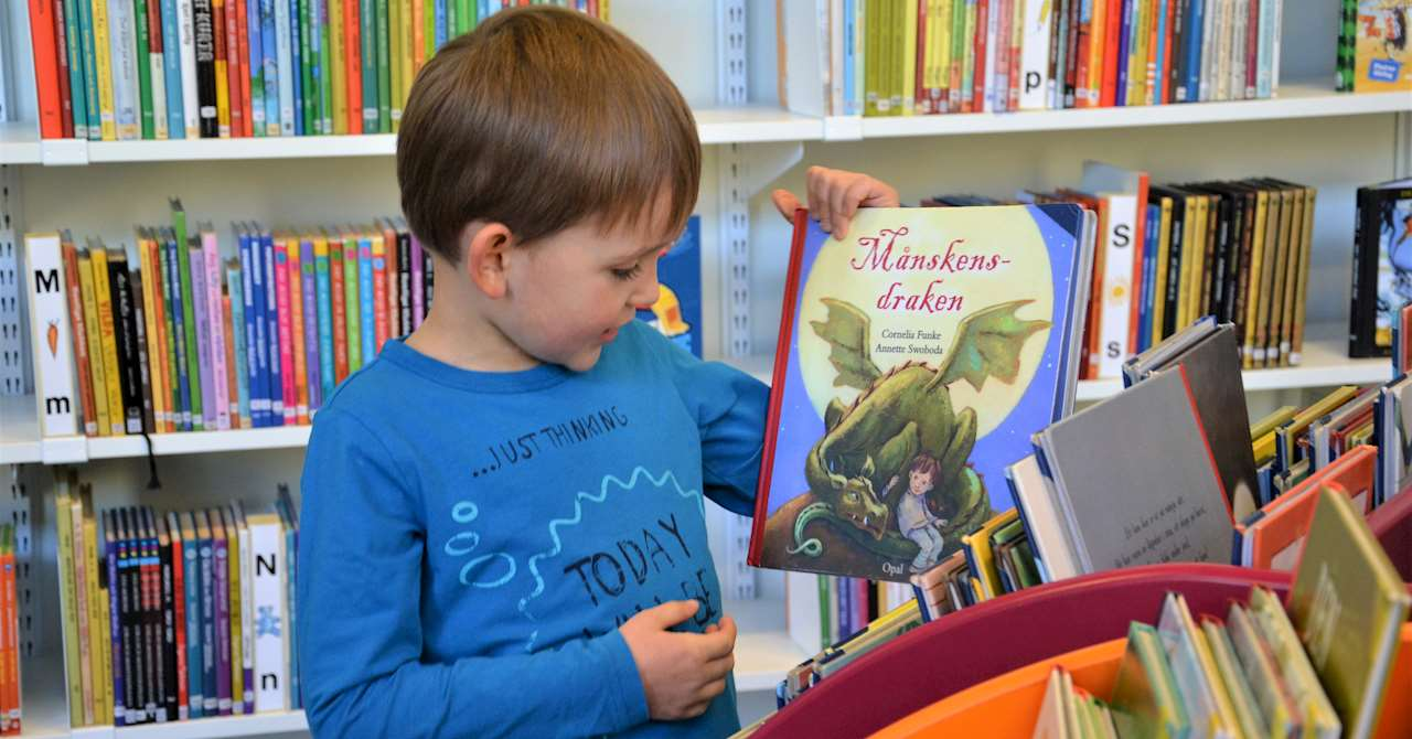 En pojke tar fram en bok ur bilderbokstråget.